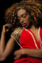 Beautiful exotic african american woman wearing a red dress drap draped in pearls with her eyes closed reclining on dark Royalty Free Stock Image