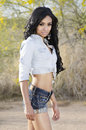 Beautiful exotic young woman long hair wearing denim jean shorts and top posing in arizona desert usa Royalty Free Stock Image