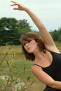 Beautiful expressive female dancer with arms exten ballet in black an pose posing outdoors trees and grass Royalty Free Stock Image