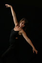 Beautiful expressive female dancer with arms extended ballet in black on a black background pose Stock Photo