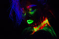 Beautiful extraterrestrial model woman with blue hair and green lips in neon light. It is close portrait of beautiful Royalty Free Stock Photo