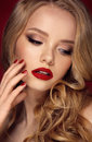 Beautiful face of a fashion model with blue eyes.Curly hair. Red lips. Studio portrait. Royalty Free Stock Photo