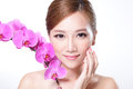 Beautiful face with pink orchids of young adult woman asian Royalty Free Stock Photo