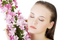 Beautiful face of spa woman with healthy clean skin and pink flowers isolated on white Stock Images