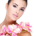 Beautiful face of woman with healthy skin young pretty and pink flowers on body isolated on white Stock Photos