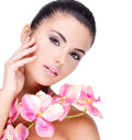 Beautiful face of woman young pretty with healthy skin and pink flowers on body isolated on white Stock Photo