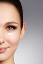 Beautiful face of young woman with cosmetic cream on a cheek. Sk Royalty Free Stock Photo
