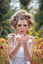 Beautiful fairy girl in a forest giving a kiss close portrait Royalty Free Stock Image