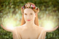 Beautiful fairy woman with glow in hands on natural green background Stock Photography