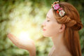 Beautiful fairy woman with glow in hands on natural green background Royalty Free Stock Images