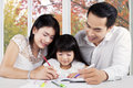 Beautiful family doing schools assignment young modern assist their child at home Stock Photo