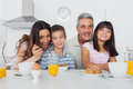 Beautiful family eating breakfast in kitchen together Royalty Free Stock Photo