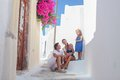 Beautiful family of four sitting on doorstep at old greek house in the street emporio santorini Royalty Free Stock Photos