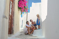 Beautiful family of four sitting on doorstep at old greek house in the street emporio santorini Royalty Free Stock Image