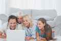 Beautiful family using a laptop lying on a carpet in the living room Royalty Free Stock Photography