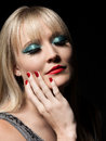Beautiful fashion glamor woman young blonde wearing jewellery and makeup sexy red lips and nails black background Stock Image