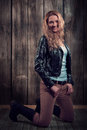 Beautiful fashion model with blond curly hair wearing black jacket pants and black tall boots in a pose on her knees lovely young Royalty Free Stock Image