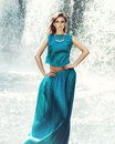 Beautiful fashion model posing in front of the waterfall Stock Images