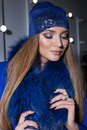 Beautiful fashion sexy elegant girl with long hair trendy blue cap on his head from evening sitting bright makeup and painting nea Royalty Free Stock Photo