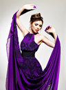 Beautiful fashion woman in purple long dress hairstyle with pigtails design poses at studio Stock Photo