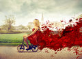 Beautiful fashion woman riding a bike with a red dress Royalty Free Stock Image