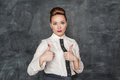 Beautiful fashion woman showing thumbs up sign on the blackboard background Royalty Free Stock Images