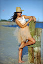 Beautiful and fashion young woman with long legs in luxury dress and hat posing on the beach Royalty Free Stock Photography