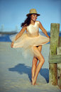 Beautiful and fashion young woman with long legs in luxury dress and hat posing on the beach Stock Images
