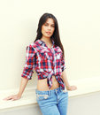 Beautiful fashion young woman wearing a checkered shirt and jeans Royalty Free Stock Photo
