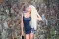 Beautiful fashionable blonde in high heels learn skateboarding. Royalty Free Stock Photo