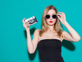 Beautiful fashionable girl posing and holding a vintage camera in black dress and sunglasses on the green background in the studio Royalty Free Stock Photo