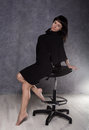 Beautiful fashionable lady wearing a gothic black dress with high collar, poses on a armchair