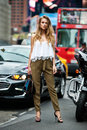 Beautiful fashionable woman standing on city street on car traffic wearing green pants, white sexy t-shirt and holding bag
