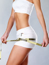 Beautiful feamle body with measuring tape. Royalty Free Stock Photo