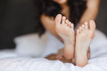 Beautiful feet, lying in the bed of a young woman Royalty Free Stock Photo