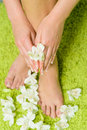 Beautiful feet with pedicure and flowers at green background Royalty Free Stock Photo