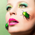Beautiful femal face with beetles female green make up and Stock Photography