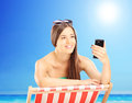 Beautiful female on a beach chair looking at mobile phone on a outside sunny day Stock Photography