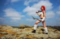 Beautiful female character with two swords on big stones Royalty Free Stock Photo