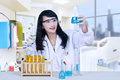 Beautiful female doctor analysing chemical in hospital is flasks at the Stock Photo
