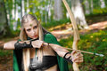 Beautiful female elf archer in the forest hunting with a bow Royalty Free Stock Photo