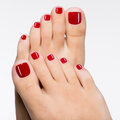 Beautiful female feet with red pedicure closeup photo of a isolated on white Royalty Free Stock Photography