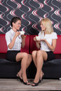 Beautiful female friends sitting with coffee cups on the sofa young Royalty Free Stock Photos