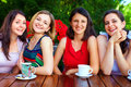 Beautiful female friends in summer cafe smiling Stock Images