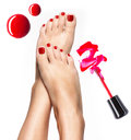 Beautiful female legs with red pedicure and nail polish bottle brush Stock Image