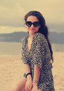 Beautiful female model in fashion sun glasses and dress sitting Royalty Free Stock Photo