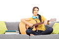 Beautiful female musician sitting on sofa and playing an acousti acoustic guitar isolated white background Stock Images