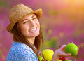Beautiful female offers an apple closeup portrait of happy laughing in floral garden bright sunset light farming and harvesting Stock Images