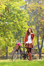 Beautiful female in park with her bicycle a Royalty Free Stock Photos