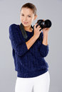 Beautiful female photographer trendy young holding a professional dslr camera and smiling at the viewer isolated on grey Stock Photography